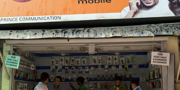 TO GO WITH India-technology-telecom, FOCUS by Penny Macrae  Advertising for Micromax mobile is seen outside a shop selling handsets in New Delhi on September 15, 2010.  During this year's IPL cricket tournament in India, mobile phone manufacturers used the hugely popular extravaganza to blitz viewers with an array of sponsorship deals and advertising. But rather than seeing the familiar big international brands, cricket fans were bombarded by nimble home-grown handset makers who saw the opportunity to reach consumers nationwide, particularly in rural areas. AFP PHOTO/Manpreet ROMANA (Photo credit should read MANPREET ROMANA/AFP/Getty Images)