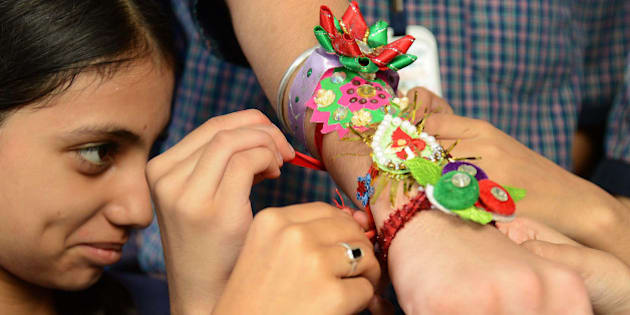 An Indian school girl ties a 'rakhi' - sacred thread - onto the wrist of a school boy on the eve of the Hindu festival Raksha Bandhan at a school in Amritsar on August 20, 2013. The annual festival of Raksha Bandhan, which commemorates the abiding ties between siblings of opposite sex, is marked by a very simple ceremony in which a woman ties a rakhi, which may be a colorful thread, a simple bracelet, or a decorative string, around the wrist of her brother.   AFP PHOTO/NARINDER NANU        (Photo credit should read NARINDER NANU/AFP/Getty Images)