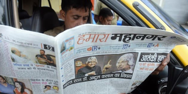 An Indian taxi driver reads a newspaper with the news of the demise of India's former president and top scientist A. P. J. Kalam at the age of 83 on its front page as he waits for a passenger in Mumbai on July 28, 2015.  Avul Pakir Jainulabdeen Abdul Kalam, commonly known as India's missile man for he played a lead role in the country's nuclear weapons tests, collapsed during a lecture at a management institute in the northeastern Indian city of Shillong, and was declared dead on arrival by doctors at the city's Bethany hospital on July 27.       AFP PHOTO / INDRANIL MUKHERJEE        (Photo credit should read INDRANIL MUKHERJEE/AFP/Getty Images)