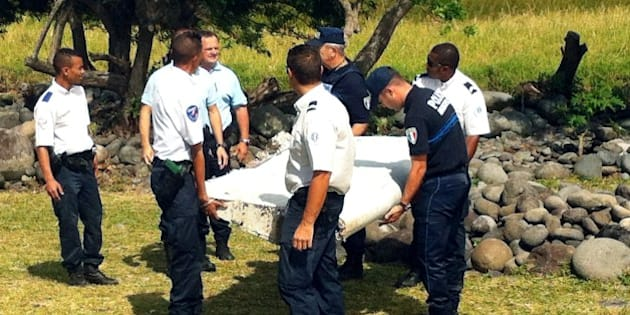 Police and gendarmes carry a piece of debris from an unidentified aircraft found in the coastal area of Saint-Andre de la Reunion, in the east of the French Indian Ocean island of La Reunion, on July 29, 2015.  The two-metre-long debris, which appears to be a piece of a wing, was found by employees of an association cleaning the area and handed over to the air transport brigade of the French gendarmerie (BGTA), who have opened an investigation. An air safety expert did not exclude it could be a part of the Malaysia Airlines flight MH370, which went missing in the Indian Ocean on March 8, 2014. AFP PHOTO / YANNICK PITOU        (Photo credit should read YANNICK PITOU/AFP/Getty Images)