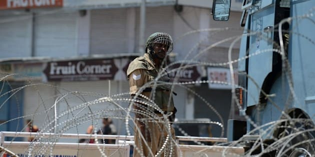 An Indian paramilitary trooper stands guard in between shuttered shops and barbed wire in Srinagar on June 17, 2015 during a one-day strike called by seperatist groups against a recent spate of mysterious killings in Indian-administered Kashmir. Six former rebels and seperatist activists have been killed in Sopore area of the disputed region during the last three weeks. AFP PHOTO/Tauseef MUSTAFA        (Photo credit should read TAUSEEF MUSTAFA/AFP/Getty Images)