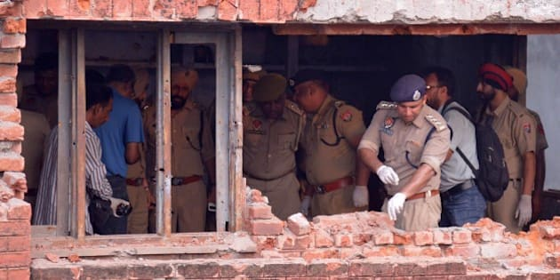 Indian police inspect a the building after armed militants attacked the police station in Dinanagar town, in the Gurdaspur district of Punjab state on July 27, 2015. Indian security forces were battling an armed attack on a police station near the Pakistan border in which at least five people have been killed. AFP PHOTO/ NARINDER NANU        (Photo credit should read NARINDER NANU/AFP/Getty Images)