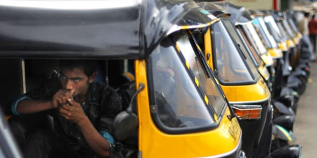 A man sits inside a motorized three wheeler called auto rickshaw, during a strike in Mumbai, India, Monday, April 16, 2012. Drivers of auto rickshaws, a popular mode of cheap transport across India, are on a day long strike in Mumbai to protest against a lower than expected hike in fares. (AP Photo/Rafiq Maqbool)