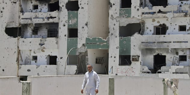 A Libyan man walks past a damaged building in Sirte on July 6, 2012 on the eve of the elections for the General National Congress. Libya's election on July 7, could well bring Islamists to power, but liberals under the leadership of the architects of the revolt that ousted Moamer Kadhafi say they too are confident of a win. AFP PHOTO/MOHAMMED ABED        (Photo credit should read MOHAMMED ABED/AFP/GettyImages)
