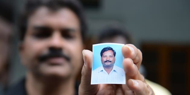 A relative holds up a photograph of Indian national, Balaram, who is thought to have been abducted in Libya, at his residence in Hyderabad on July 31, 2015.  Four Indian teachers working in Libya have been 'detained' as they tried to travel home, New Delhi said July 31, sparking fears they are being held by the Islamic State group.  India's foreign ministry said the group was detained at a checkpoint around 31 miles (50 kilometres) from Sirte late July 30, and taken to the southern coastal city, which the jihadist group claims to control.    AFP PHOTO/ NOAH SEELAM        (Photo credit should read NOAH SEELAM/AFP/Getty Images)