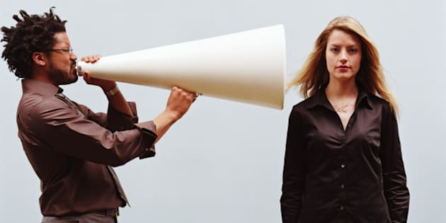 Man yelling into megaphone pointed at young woman's ear