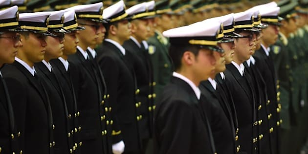 Graduates of the National Defense Academy wearing uniforms of the Self-Defense Forces attend their cadet appointment ceremony in Yokosuka, Kanagawa Prefecture on March 22, 2015.  A total of 492 students graduated from the school this year. AFP PHOTO / KAZUHIRO NOGI        (Photo credit should read KAZUHIRO NOGI/AFP/Getty Images)