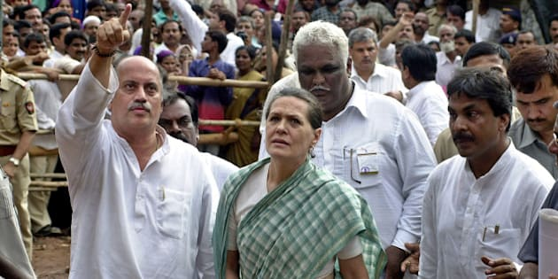 Maharashtra Congress President Gurudas Kamat, left, points towards the landslide site as Congress party President Sonia Gandhi, center, looks on at Saki Naka, a suburb of Bombay, India, Saturday, Aug. 13, 2005, where a landslide caused by rainwater killed 45 people on July 26. Gandhi is on a visit to the city that is battling waterborne diseases which has killed at least 66 people, after the city was crippled by rainwater floods. (AP Photo/Rajesh Nirgude)