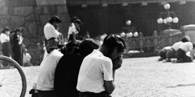 Schoolgirls weep in sorrow and shame in the Imperial Plaza before Emperor Hirohito's palace in Tokyo after there were informed of Japan's surrender, Aug. 15, 1945.  Some officers of the Imperial Army committed harikiri in the plaza to atone for what they felt was a loss of face for themselves and their emperor. (AP Photo)
