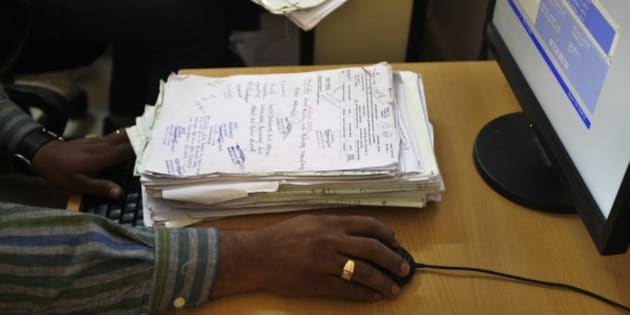In this Dec. 10, 2012 photo, a government official enter authorized land records in a computer at the government registrar's office in Hoskote 30 Kilometers (19 miles) from Bangalore in the southern Indian state of Karnataka. For years, Karnataka's land records were a quagmire of disputed, forged documents maintained by thousands of tyrannical bureaucrats who demanded bribes to do their jobs. In 2002, there were hopes that this was about to change. (AP Photo/Aijaz Rahi)