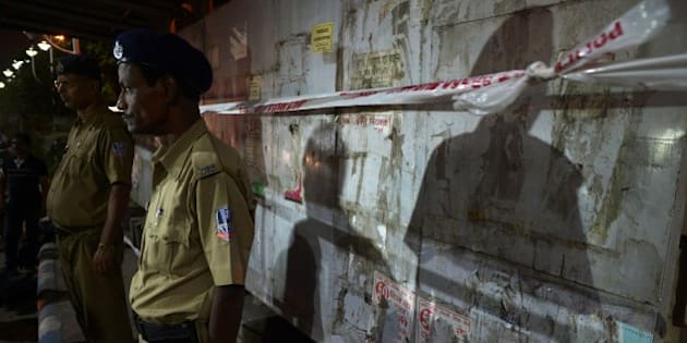 West Bengal state police personel stand guarding the bomb blast spot next to the Central Reserve Police Force(CRPF) camp  in Kolkata on November 10, 2014. Bangladesh national Seikh Rahmatulla alias Sajid claimed to be the chief of Jamaat-ul-Mujahideen Bangladesh(JMD) terror module in the recent Burdwan blast is kept inside the CRPF camp after National Investigation Agency (NIA) arrested him. AFP PHOTO/Dibyangshu SARKAR        (Photo credit should read DIBYANGSHU SARKAR/AFP/Getty Images)