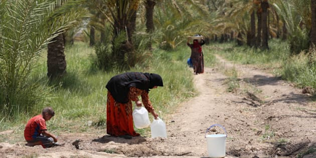 Iraqis displaced by conflict collect water at al-Takia refugee camp in Baghdad, Iraq, Thursday, July 30, 2015. Scorching temperatures are normal this time of year, but an unprecedented heat wave prompted Iraqi authorities to declare a mandatory four-day holiday beginning Thursday. The government has urged residents to stay out of the sun and drink plenty of water. (AP Photo/ Khalid Mohammed)