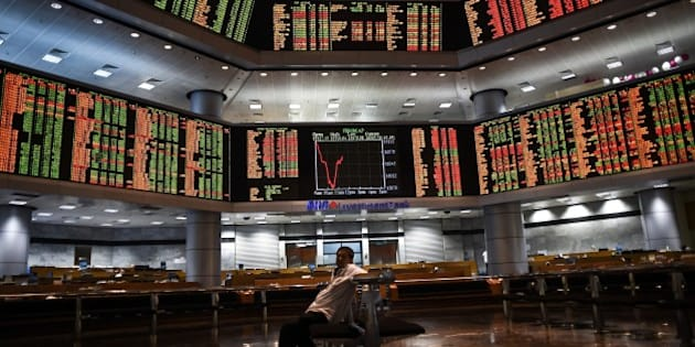 A man sits before electronic boards showing stock movements at the Malaysia Stock Exchange in Kuala Lumpur on July 28, 2015.  Asian markets tumbled further dragged down by another massive sell-off in Shanghai a day after the mainland Chinese market's heaviest one-day losses in more than eight years.  AFP PHOTO / MANAN VATSYAYANA        (Photo credit should read MANAN VATSYAYANA/AFP/Getty Images)