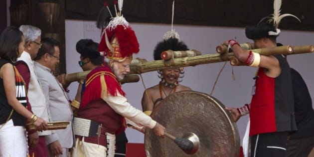 Indian Prime Minister Narendra Modi, third right, dressed in Naga attire hits a traditional musical instrument to inaugurate the Hornbill festival in Kisama village in Nagaland, India, Monday, Dec. 1  2014. The 10-day long festival named after the Hornbill bird is one of the biggest festivals that showcases the rich tradition and cultural heritage of the indigenous Nagas of India's northeast. (AP Photo/Anupam Nath)