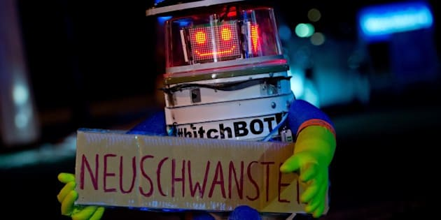 Robot 'hitchBOT' is seen holding a sign reading 'Neuschwanstein' as he waits for a lift at the roadside in Munich, southern Germany, on February 13, 2015. HitchBOT, a charming robot assembled using household parts who was hitchhiking more than 6,000 kilometers across Canada in summer 2014 as part of a social experiment, started his tour across Germany, where he is aimed to visit among others Neuschwanstein Castle in the South, the carnival in Cologne (West), the North Sea island of Sylt, the eastern city of Goerlitz near the Polish border and the German capital Berlin.            AFP PHOTO / DPA / SVEN HOPPE   +++   GERMANY OUT        (Photo credit should read SVEN HOPPE/AFP/Getty Images)