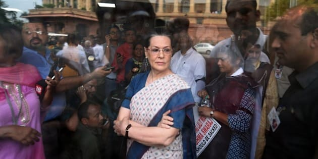 Congress President Sonia Gandhi (C) waits for Vice President Rahul Gandhi and former Prime Minister Manmohan Singh to address the media after a protest by Congress Party Members of Parliament at the Mahatma Gandhi statue outside Parliament house in New Delhi on August 4, 2015. Congress MPs protested outside Parliament, including former Prime Minister Manmohan Singh, Congress vice-president Rahul Gandhi and other senior party leaders who raised slogans against Prime Minister Narendra Modi and the NDA government following the suspension of 25 of their MPs, and demanded the resignation of Foreign Minister Sushma Swaraj.  AFP PHOTO/ PRAKASH SINGH          (Photo credit should read PRAKASH SINGH/AFP/Getty Images)