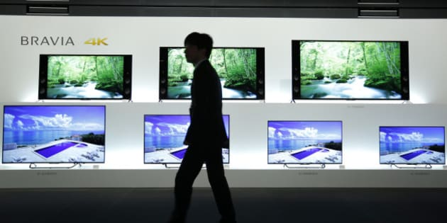 An attendant walks past Sony Corp. Bravia 4K liquid crystal display (LCD) televisions displayed at a launch event in Tokyo, Japan, on Wednesday, May 13, 2015. Sony's TV making unit had a profit of 8.3 billion yen in the year ended March -- its first in 11 years. Photographer: Kiyoshi Ota/Bloomberg via Getty Images