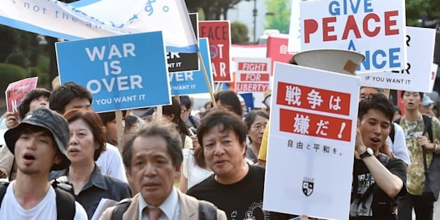 Students and scholars stage a demonstration march to protest against controversial security bills which would expand the remit of the country's armed forces, in front of the National Diet in Tokyo on July 31, 2015. The security bills, which Japan's Prime Minister Shinzo Abe and his supporters say are necessary for Japan to deal with the world around it, are deeply unpopular in the country at large.  AFP PHOTO / KAZUHIRO NOGI        (Photo credit should read KAZUHIRO NOGI/AFP/Getty Images)