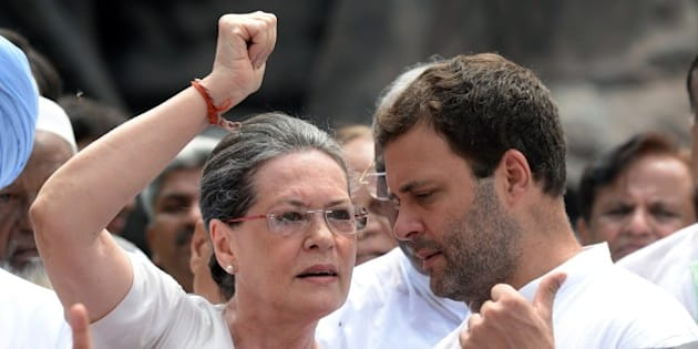 Congress Party President Sonia Gandhi (L) talks with the party vice president and son Rahul Gandhi (R) as they join other Congress Party members of parliament to shout slogans against Prime Minister Narendra Modi and the NDA government at Parliament House in New Delhi on August 5, 2015. Members of the Congress Party, supported by other parties, protested against the suspension of 25 Congress MPs for ''willfully'' disrupting proceedings in the Indian parliament. AFP PHOTO/PRAKASH SINGH        (Photo credit should read PRAKASH SINGH/AFP/Getty Images)