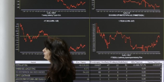 An employee of the Stock Exchange passes a display showing stock price movements in Athens, Wednesday, April 9, 2014. Greece confirmed Wednesday that it is returning to international bond markets for the first time in four years amid growing signs of confidence in the country that triggered the European debt crisis. (AP Photo/Thanassis Stavrakis)