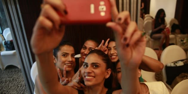 An Indian model takes a photograph of herself with other models on a mobile phone as they wait to participate in an audition for the upcoming Lakme Fashion Week, in Mumbai, India, Thursday, July 3, 2014. The event is scheduled to begin August 20, 2014 in Mumbai. (AP Photo/Rafiq Maqbool)