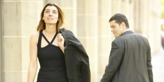 Businessman staring at woman walking on sidewalk
