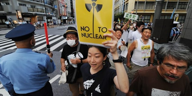 People hold placards and shout slogans as they attend an anti nuclear power rally on a street in Tokyo on August 18, 2012. The rally came after Japan on August 15 marked the 67th anniversary of its surrender, which came after the United States dropped nuclear bombs on Hiroshima and Nagasaki.    AFP PHOTO / Toru YAMANAKA        (Photo credit should read TORU YAMANAKA/AFP/GettyImages)