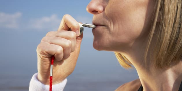 Woman blowing whistle on beach
