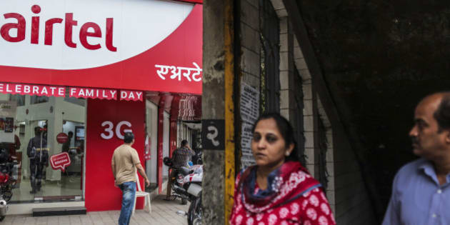 Pedestrian walk past a Bharti Airtel Ltd. store in Mumbai, India, on Saturday, Feb. 28, 2015. The government auction of telecom wireless spectrum starting March 4 is expected to raise as much as $15.6 billion from service providers including those controlled by billionaires Kumar Mangalam Birla, Sunil Mittal and Anil Ambani, according to ICRA Ltd. Photographer: Dhiraj Singh/Bloomberg via Getty Images