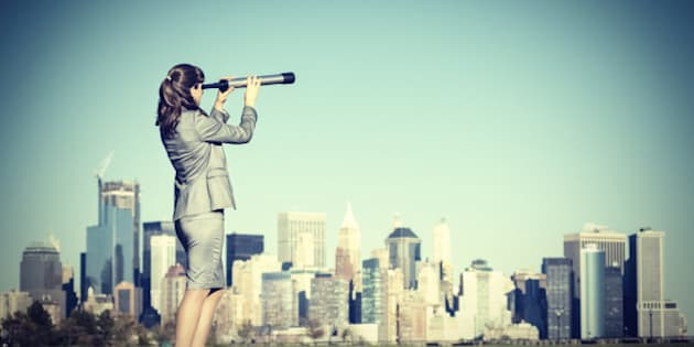 Business woman with spyglass looking for new business opportunities.