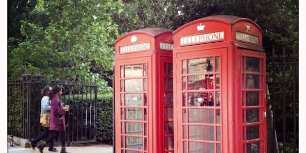 Old fashioned British telephone boxes at the entrance to Russell Square, London, UK.