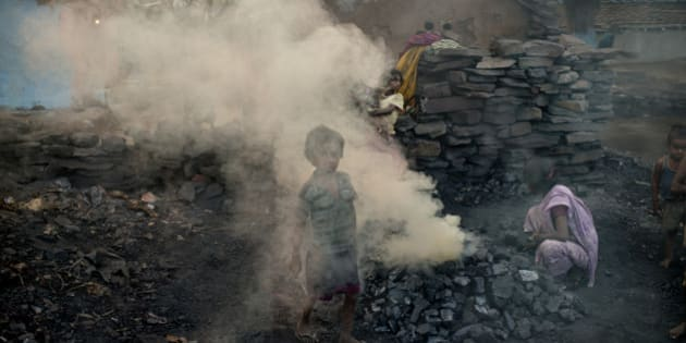 JHARIA, JHARKAND, INDIA - 2014/10/24: A child walks through a cloud of smoke in a village located between one the coal mines. Methane and other toxic gases spew from the open wounds in the crust near coal mines in Jharia. 