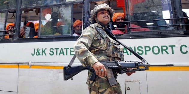 JAMMU, INDIA - AUGUST 5: A CRPF soldier guards the bus carrying passengers of the Amarnath Yatra which was halted due to the terrorist attack on BSF convoy at Jammu-Srinagar national highway on August 5, 2015 in Udhampur near Jammu, India. A terrorist, identified as Mohammed Naved Yakub, son of Mohammed Yakub from Faisalabad in Pakistan and belong to Lashkar-e-Taiba terror group, was nabbed by the Village Defence Committee members after the attack. While his fellow terrorist identified as Noman alias Momin was killed in the gun fight. Two BSF soldiers also lost their life. (Photo by Nitin Kanotra/Hindustan Times via Getty Images)