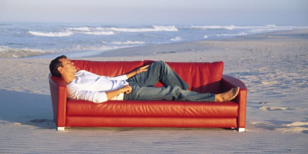 Man lying on sofa at beach