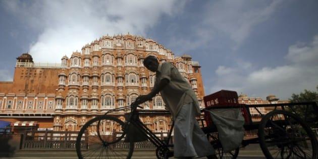 An Indian man pulls a rickshaw past the 'Hawa Mahal' or the Palace of Winds in Jaipur, India, Monday, Sept. 8, 2014. (AP Photo/ Deepak Sharma)