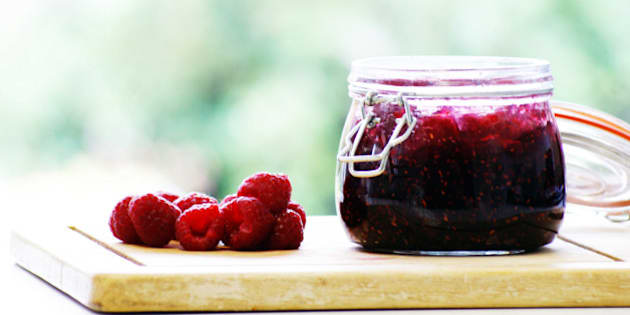 Delicious home-made raspberry jam in a jar and fresh raspberries on the side.
