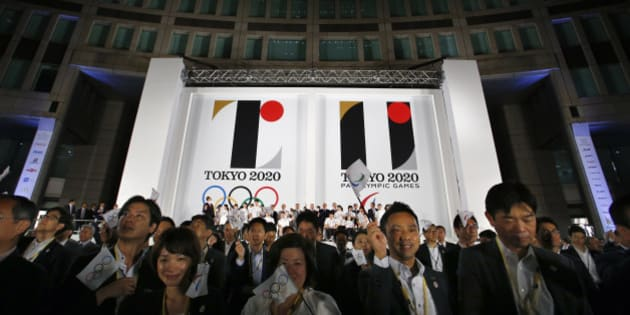 Visitors wave a flag for the Olympics and Paralympics in front of a official Emblems of the Tokyo 2020 Olympic and Paralympic Games at Tokyo Metropolitan Plaza in Tokyo, Friday, July 24, 2015. (AP Photo/Shizuo Kambayashi)