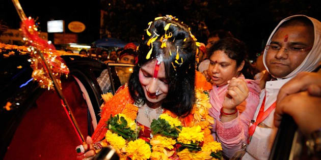 MUMBAI, INDIA - AUGUST 27: (file photo) Radhe Maa, self-proclaimed Godwoman, visits Siddhivinayak Temple, Prabhadevi, on August 27, 2012 in Mumbai, India. Radhe Maa has been accused of dowry harassment by a woman, who has filed an FIR or police complaint in Mumbai. The woman has said that her husband's family tortured her on the godwoman's advice and forced her to serve Radhe Maa, do chores for her and give her massages. Radhe Maa's real name is Sukhvinder Kaur. She was born on 4 April 1965 in Dorangala village of Gurdaspur district in Punjab. Her followers state that she was drawn to spirituality as a child, and spent a lot of time at the Kali temple in her village. However, according to people of her village, she did not show any spiritual leanings as a child. At the age of 23, she became a disciple of Mahant Ram Deen Das of 1008 Paramhans Bagh Dera Mukerian in Hoshiarpur district. Ram Deen Das oversaw her deeksha (initiation ceremony), and gave her the title Radhe Maa. She is usually seen in glittering red bridal wear, heavy jewellery and layers of make-up. Thick garlands and a trident complete the picture. She used to stitch clothes to support her husband's small income. (Photo by Vijayanand Gupta/Hindustan Times via Getty Images)