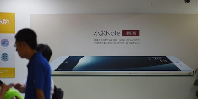 Customers wait near an advertisement for the Xiaomi Note mobile phone at a Xiaomi service center in Beijing on August 5, 2015.  Chinese company Xiaomi was the largest smartphone vendor in China based on shipments with a 15.9 percent market share in the second quarter of 2015, according to Canalys. Telecom equipment maker Huawei was close behind at 15.7 percent, it said, followed by Apple, South Korea's Samsung and Chinese firm Vivo. AFP PHOTO / GREG BAKER        (Photo credit should read GREG BAKER/AFP/Getty Images)