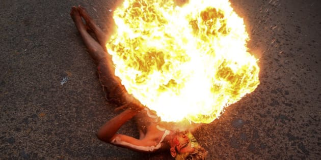 "An Indian artist performs with fire during a procession as part of ""Bonalu"" festival in Hyderabad, India, Monday, Aug.10, 2015. Bonalu is a month long Hindu folk festival of India's Telangana region dedicated to Kali, the Hindu goddess of destruction. (AP Photo/Mahesh Kumar A.)"