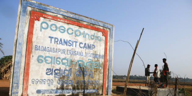 Signage for the Posco India Transit Camp, where families relocated from the site of a proposed Posco steel plant have been provided temporary shelter, stands in Badagabapur, Odisha, India, on Sunday, Jan. 19, 2014. Posco may soon start construction on a $12 billion steel complex in India first proposed in 2005 as Prime Minister Manmohan Singh speeds up the approval process for the nations biggest foreign investment. Photographer: Prashanth Vishwanathan/Bloomberg via Getty Images