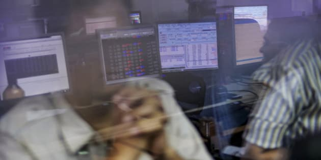 Employees are reflected in a glass panel as they use desktop computers while monitoring data at a securities brokerage in Mumbai, India, on Tuesday, Aug. 4, 2015. Indian central bank Governor Raghuram Rajan kept interest rates unchanged, rebuffing pressure from the Finance Ministry to reduce borrowing costs that are among the highest in Asia. Photographer: Dhiraj Singh/Bloomberg via Getty Images
