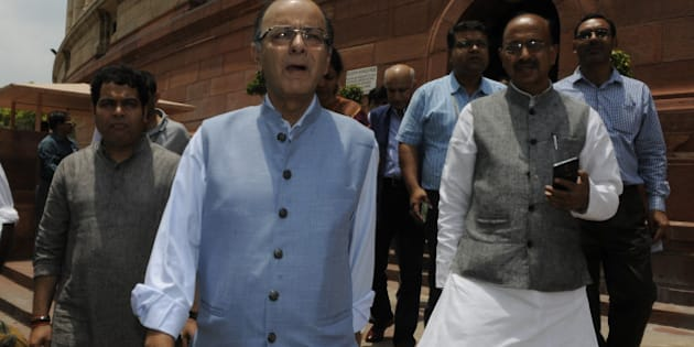 NEW DELHI, INDIA - JULY 21: Union Finance Minister Arun Jaitley (C) with BJP National Media Convener Shrikant Sharma (L) and Rajya Sabha MP Vijay Goel going to address the media after adjourned Rajya Sabha on the first day of monsoon session at Parliament House on July 21, 2015 in New Delhi, India. The monsoon session of Parliament started on a stormy note on Tuesday with Congress and other opposition parties stalling proceedings, demanding the resignation of External Affairs Minister Sushma Swaraj and two Chief Ministers over the Lalit Modi controversy and the Vyapam scam. (Photo by Sonu Mehta/Hindustan Times via Getty Images)