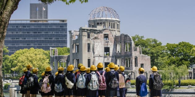 Children standing near Atomic Bomb memorial in Hiroshima, Japan. A-Bomb (Genbaku) Dome, Hiroshima, Japan. The Genbaku Dome also known as the Atomic Bomb Dome is now a symbol for peace within the Hiroshima Peace Memorial Park. The building designed by Jan Letzel, a Czech architect, was completed in 1915. The building was one of the few left standing when the first atomic bomb 'Little Boy' was dropped from the Enola Gay on August 6, 1945.