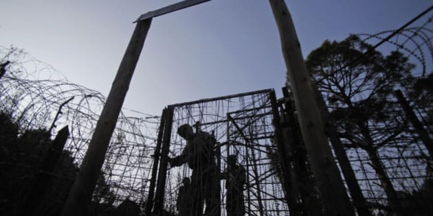 In this Monday, Dec. 23, 2013 photo, Indian army soldiers patrol near the India-Pakistan border fencing at the Line of Control (LOC), that divides Kashmir between India and Pakistan, at Krishna Ghati (KG Sector) in Poonch, 290 kilometers (180 miles) from Jammu, India. The military commanders of longtime rivals India and Pakistan met on Tuesday in a bid to stop frequent cross-border attacks in disputed Kashmir which escalated tensions in the region in recent months. (AP Photo/Channi Anand)