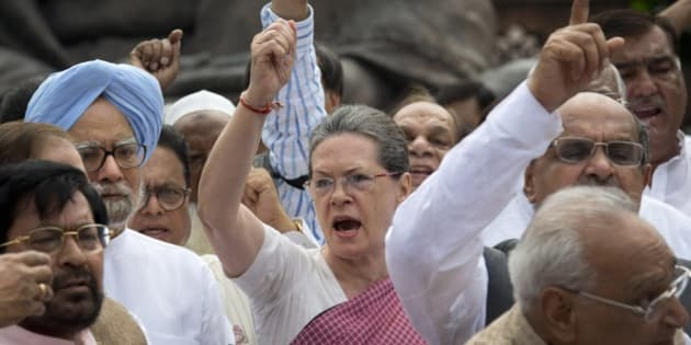 Former Indian Prime Minister Manmohan Singh, left in blue turban, watches as India's opposition Congress party president Sonia Gandhi, center, and other lawmakers shout slogans against the government during a protest in the parliament premises in New Delhi, India, Wednesday, Aug. 5, 2015. The opposition has been demanding that two leaders of the ruling Bharatiya Janata Party resign for allegedly helping a former Indian cricket official facing investigation for financial irregularities. (AP Photo/Manish Swarup)