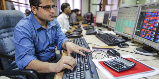 Employees use desktop computers as they monitor data at a securities brokerage in Mumbai, India, on Tuesday, Aug. 4, 2015. Indian central bank Governor Raghuram Rajan kept interest rates unchanged, rebuffing pressure from the Finance Ministry to reduce borrowing costs that are among the highest in Asia. Photographer: Dhiraj Singh/Bloomberg via Getty Images