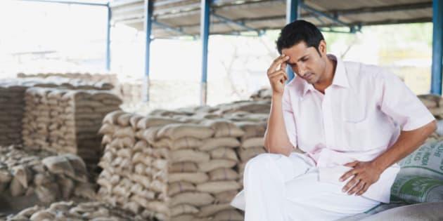 Stressed man sitting on a stack of sacks in warehouse, Anaj Mandi, Sohna, Gurgaon, Haryana, India