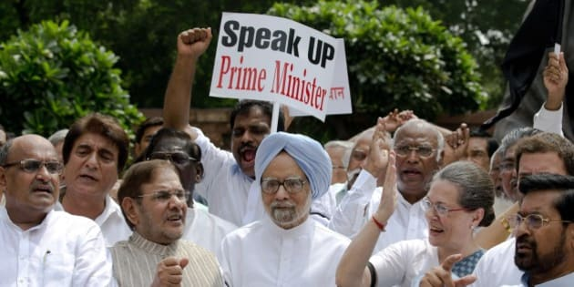 India's former prime minister Manmohan Singh, center, joins Congress party president Sonia Gandhi, second right and other opposition lawmakers shouting slogans during a protest in the Parliament premises in New Delhi, India, Thursday, Aug. 6, 2015. The opposition continued their protests Thursday demanding that two leaders of the ruling Bharatiya Janata Party resign for allegedly helping a former Indian cricket official facing investigation for financial irregularities. (AP Photo/Manish Swarup)