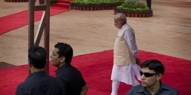 Indian Prime Minister Narendra Modi walks to receive President Pranab Mukherjee during a ceremonial reception of Mozambican President Filipe Jacinto Nyusi at the Presidential Palace in New Delhi, India, Wednesday, Aug. 5, 2015. The Indian Parliament has been unable to conduct any business for weeks as the opposition has been demanding the resignation of Sushma Swaraj and another leader for allegedly helping a former Indian cricket official facing investigation for financial irregularities. (AP Photo/Manish Swarup)